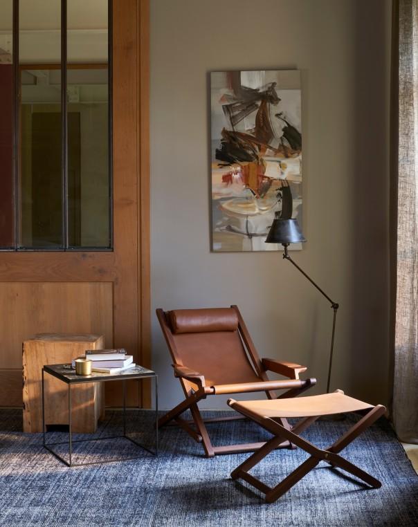 Un fauteuil bas en cuir pleine fleur avec repose-pied pour se décontracter. Duvivier